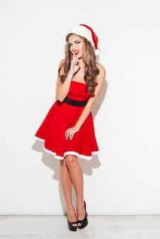 Ritratto a figura intera di un'affascinante donna graziosa in costume natalizio in piedi isolata su una superficie bianca