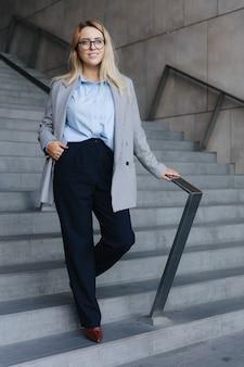 Ritratto a figura intera di donna affascinante in abiti da ufficio alla moda in piedi sui gradini dell'edificio per uffici. signora di affari con capelli biondi che sorride e che osserva da parte.
