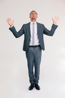 Ritratto a figura intera di un allegro uomo d'affari che si trova isolato