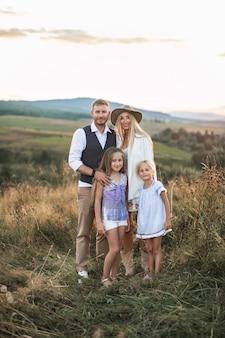 Ritratto integrale di allegra famiglia caucasica, madre, padre e due piccole figlie, in piedi nel campo selvaggio estivo
