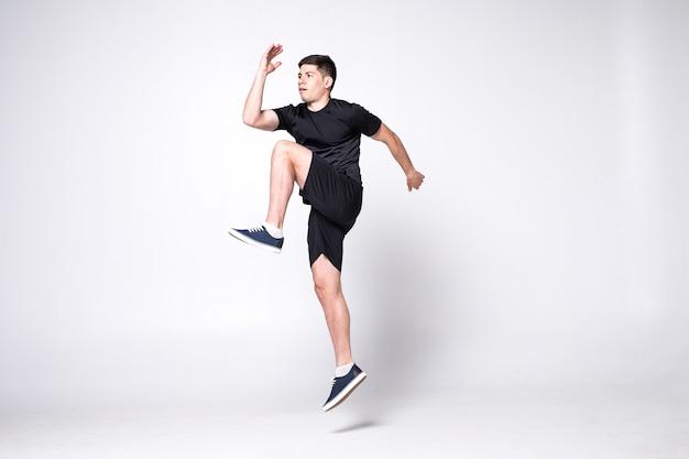Ritratto integrale di un uomo allegro di forma fisica che salta isolato su una parete bianca