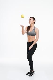 Ritratto a figura intera di una giovane donna allegra fitness in piedi e lanciando una mela in aria isolata