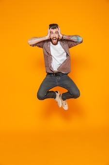 Ritratto integrale di un giovane allegro che indossa abiti casual saltando