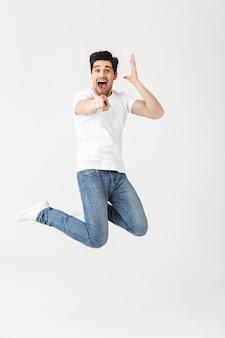 Ritratto a figura intera di un giovane allegro che indossa abiti casual isolati su bianco, presentando lo spazio della copia, saltando