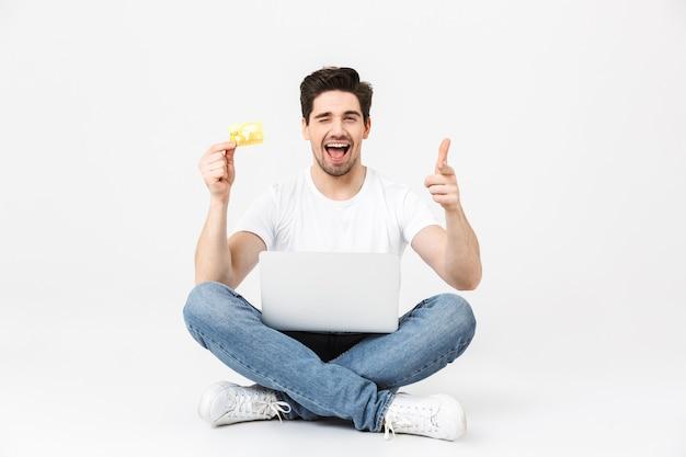 Ritratto a figura intera di un giovane allegro che indossa abiti casual isolati su bianco, seduto con un computer portatile, mostrando la carta di credito, celebrando