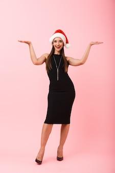 Ritratto integrale di un vestito da portare allegro della giovane donna che celebra il natale isolato sopra fondo rosa, presentante lo spazio della copia