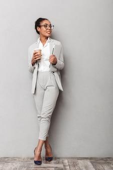 Ritratto integrale di una donna d'affari africana fiduciosa che indossa tuta in piedi, tenendo il caffè da asporto, portando laptop