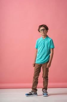Ritratto a figura intera di un ragazzo fiducioso in un vestito alla moda e occhiali