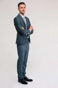 Ritratto integrale di un uomo d'affari sicuro che sta con le armi piegate isolate. guardando la telecamera