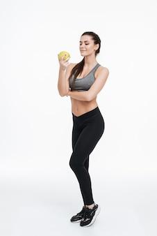 Ritratto a figura intera di una donna sportiva focalizzata fiduciosa in piedi e guardando la mela in mano isolata