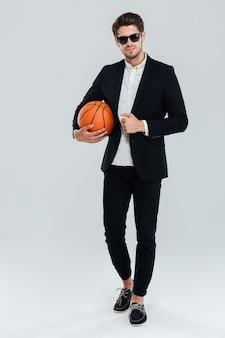 Ritratto a figura intera di un bell'uomo fiducioso in occhiali da sole e abito nero che tiene palla da basket su muro grigio
