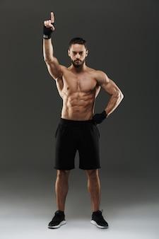 Ritratto integrale di una posa muscolare sicura dell'uomo