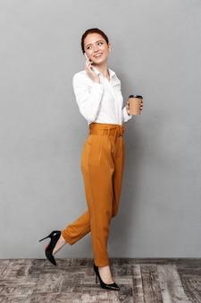 Ritratto a figura intera di donna d'affari rossa sicura che utilizza smartphone in ufficio e beve caffè da asporto dal bicchiere di plastica isolato su grigio