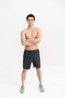 Ritratto integrale di uno sportivo fiducioso in piedi sopra bianco, braccia conserte