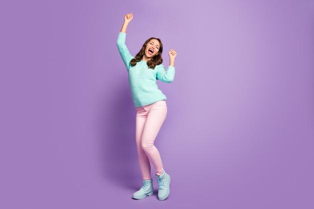 Ritratto integrale di pazza signora ondulata che urla alza i pugni che si rallegra per la festa degli studenti freddi che celebra indossare pantaloni rosa pullover soffici calzature pastello.