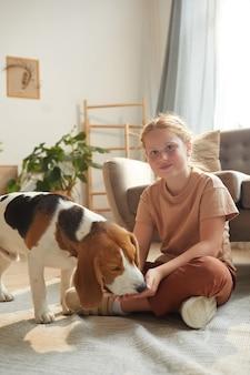 Ritratto a figura intera della ragazza dai capelli rossi carina che gioca con il cane seduto sul pavimento in interni domestici accoglienti illuminati dalla luce solare.