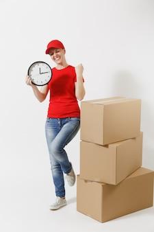 Ritratto integrale della donna di consegna in berretto rosso, maglietta isolata su fondo bianco. corriere femminile vicino a scatole di cartone vuote, con orologio rotondo, che mostra in tempo. ricezione pacco. copia spazio.