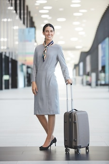 Ritratto integrale di assistente di volo elegante e sorridente mentre posa con la valigia in aeroporto