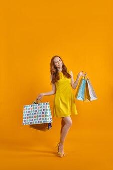 Il ritratto a figura intera di una modella eccitata porta molti pacchi godendosi lo shopping di vendite all'estero indossando t...