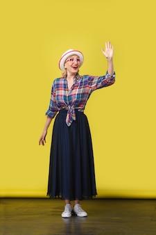Ritratto a figura intera di eccitato moderno elegante donna matura in stile casual con cappello, occhiali in piedi, agitando la mano e guardando con un sorriso a trentadue denti. studio al coperto girato su sfondo muro giallo.