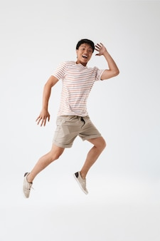 Ritratto integrale di un giovane uomo asiatico eccitato