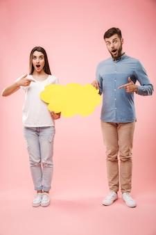Ritratto integrale di una giovane coppia eccitata che indica
