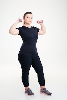 Ritratto a figura intera di una donna grassa in allenamento sportivo con manubri isolati su un muro bianco