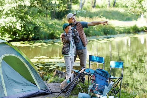 Ritratto integrale del padre e del figlio che esaminano il lago e che indicano via mentre godono insieme del viaggio di campeggio, spazio della copia