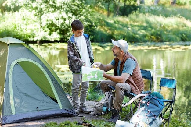 Ritratto integrale del padre e del figlio che esaminano la mappa mentre godono insieme del viaggio di campeggio dal lago, spazio della copia