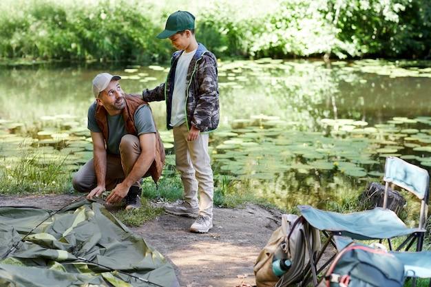Ritratto integrale del padre e del figlio che installano la tenda mentre si accampano insieme sul lago, lo spazio della copia