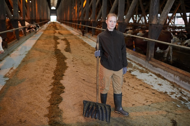 Ritratto integrale della lavoratrice agricola femminile che guarda l'obbiettivo durante la pulizia della stalla al ranch di famiglia, copia dello spazio