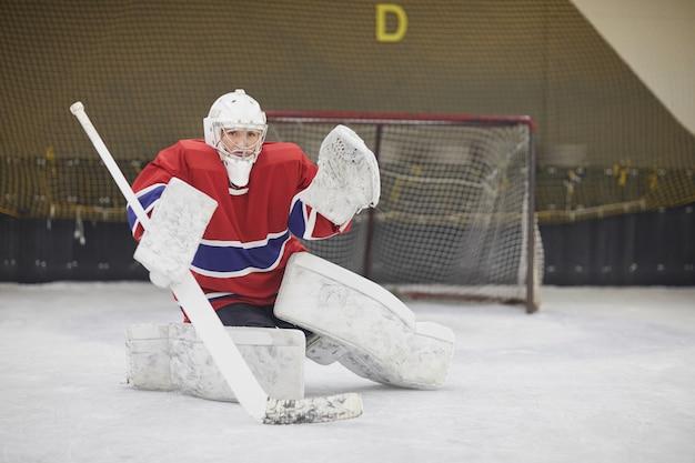 Ritratto integrale del giocatore di hockey femminile in piena marcia