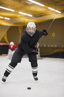 Ritratto integrale del giocatore di hockey femminile che conduce spennare durante la pratica sul ghiaccio