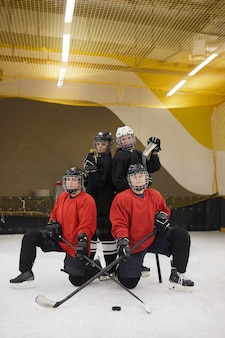 Ritratto integrale della squadra di hockey femminile in posa sulla pista durante la pratica