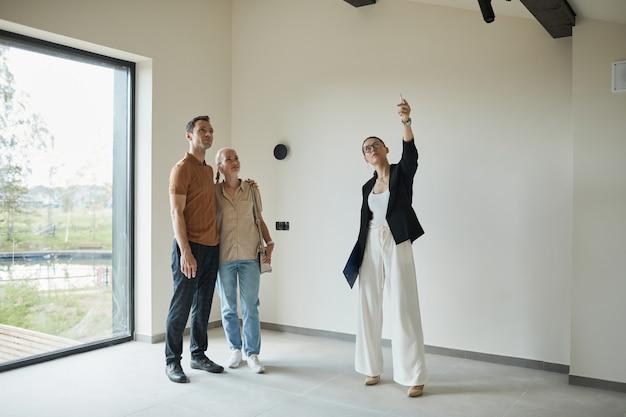 Ritratto a figura intera di agente immobiliare femminile che offre tour dell'appartamento a giovani coppie che acquistano nuove proprietà, copia spazio