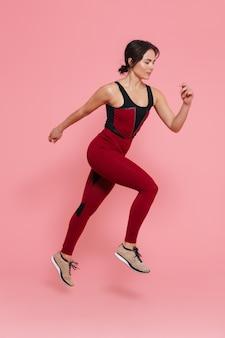 Ritratto a figura intera di una bella donna sportiva in forma che fa esercizi isolati sul muro rosa, saltando