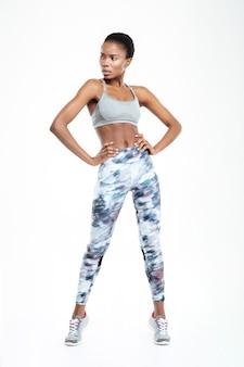 Ritratto a figura intera di una donna afroamericana fitness che guarda lontano isolata su uno sfondo bianco