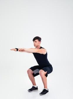Ritratto a figura intera di un uomo di forma fisica che fa esercizi accovacciati isolato
