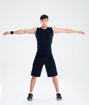 Ritratto a figura intera di un uomo di fitness che fa esercizi di riscaldamento isolato