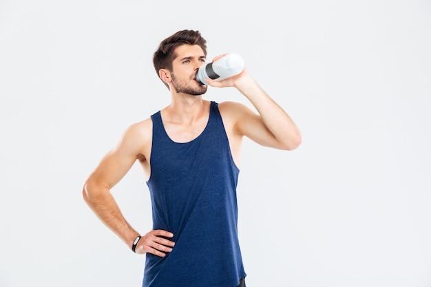 Ritratto a figura intera di un uomo di forma fisica che beve acqua isolata sullo sfondo grigio