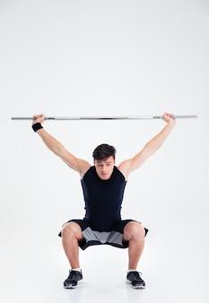 Ritratto a figura intera di un uomo di forma fisica accovacciato con bilanciere isolato