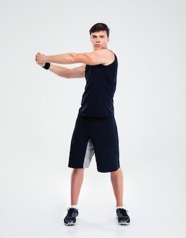 Ritratto integrale di un uomo di forma fisica che allunga le mani isolate