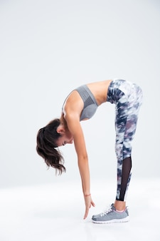 Ritratto integrale di un allenamento di donna fitness isolato su un muro bianco