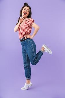Ritratto a figura intera di una pin-up che flirta in stile americano che sorride alla telecamera isolata sul muro viola