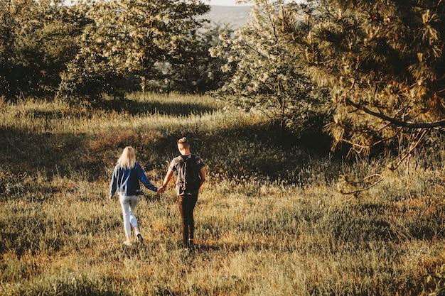 Ritratto integrale dal retro di una coppia adorabile che tiene per mano ed esplora nuovi posti durante il viaggio