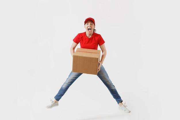 Ritratto integrale della donna di consegna di divertimento in berretto rosso, t-shirt isolata su fondo bianco. corriere o rivenditore femminile che salta con una scatola di cartone vuota. ricezione pacco. copia spazio per la pubblicità.