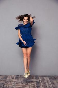 Ritratto a figura intera di una donna che ride divertente che salta sul muro grigio
