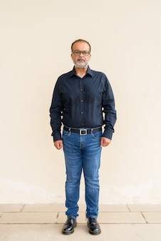 Ritratto a figura intera di un bell'uomo indiano barbuto contro un muro semplice