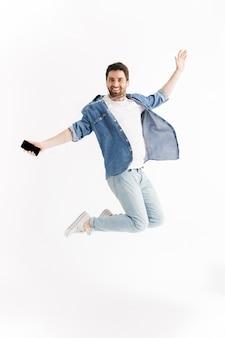 Ritratto a figura intera di un bell'uomo barbuto che indossa abiti casual che salta isolato, ascolta musica con gli auricolari, tiene in mano il cellulare, balla