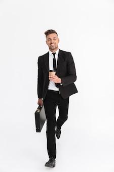 Ritratto a figura intera di un bell'uomo d'affari fiducioso che indossa un abito che cammina isolato, porta una valigetta, beve caffè